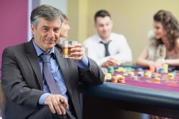 Trinkender whisky des mannes am roulettetisch