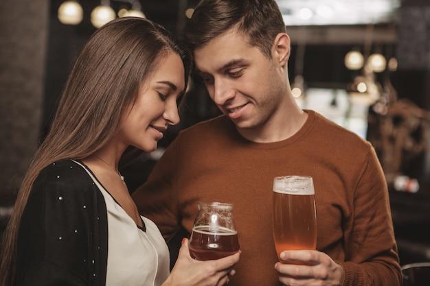 Trinkendes bier der glücklichen jungen paare auf einem datum an der bar