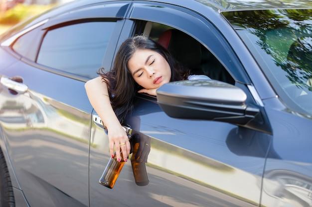 Trinkendes bier der jungen asiatischen frau beim autofahren.