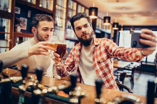 Trinkendes bier des hübschen bärtigen mannes zwei in der kneipe