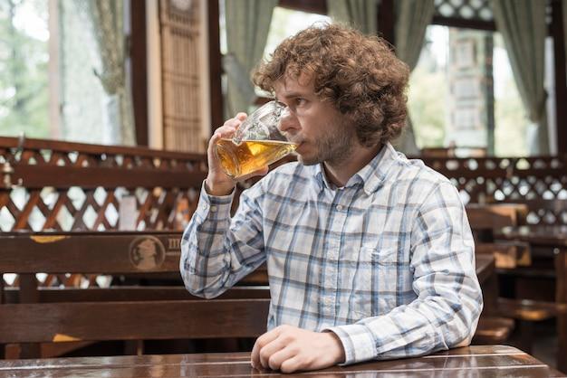 Trinkendes bier des hübschen kerls und weg schauen