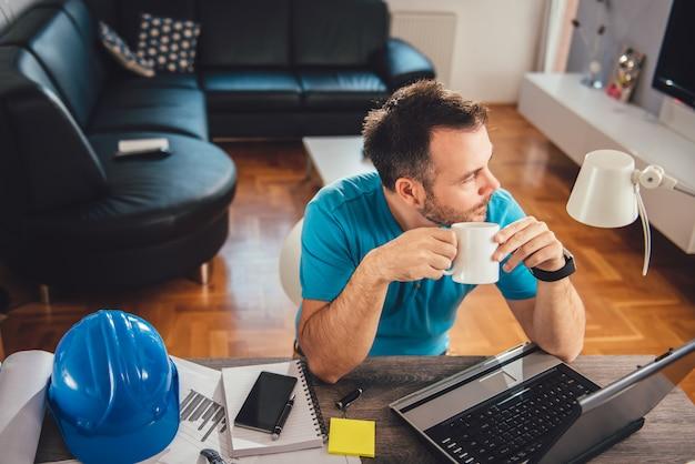 Trinkendes büro des kaffees des mannes zu hause