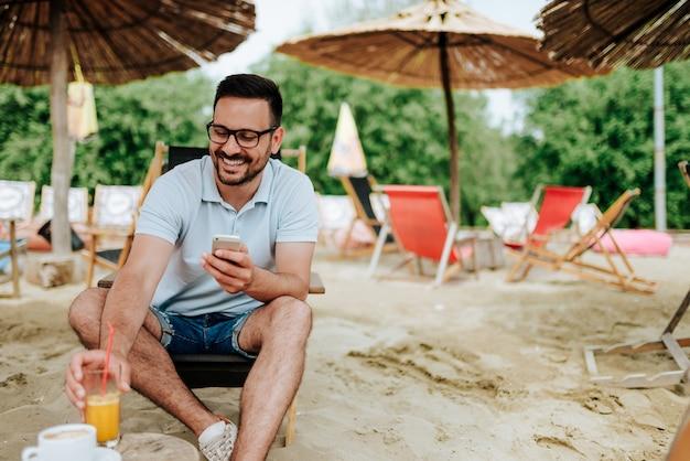 Trinkendes cocktail smilling-mannes am strand und unter verwendung des telefons.