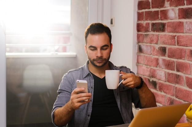 Trinkendes cofee des hübschen kerls beim hodling des telefons