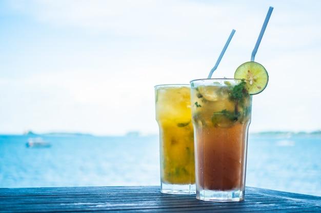 Trinkendes glas des eismojito mit tropischem seeozean
