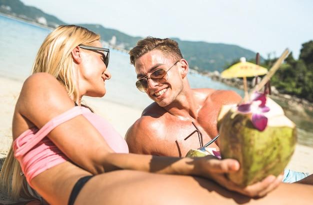 Trinkendes kokosnusscocktail der paare am tropischen strand