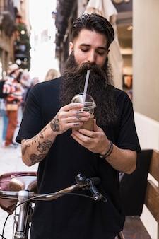 Trinkendes schokoladengetränk des bärtigen mannes, das mit fahrrad auf stadtstraße steht
