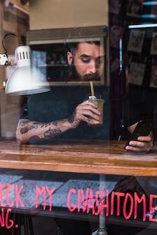 Trinkendes schokoladengetränk des mannes bei der anwendung des handys im café