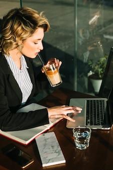 Trinkendes schokoladenmilchshake der geschäftsfrau bei der anwendung des laptops im restaurant