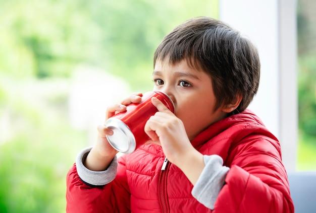 Trinkendes soda des porträtkindes, kind, das aus fenster, ungesundem lebensmittel und getränk heraus nach kinderkonzept sucht