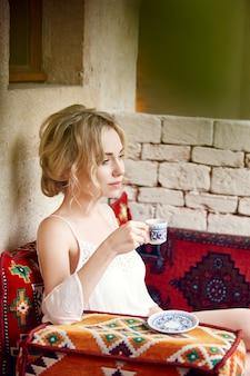 Trinkendes stillstehendes sitzen des kaffees der morgenfrau auf einem türkischen sofa. träumende frau, schöne blonde frisur, heißer tee in einer schale in ihren händen