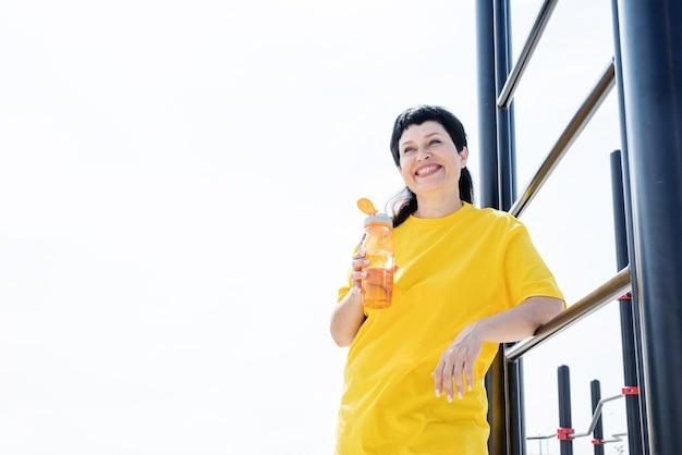 Trinkendes trinkwasser der älteren frau nach dem training im freien auf dem sportplatz
