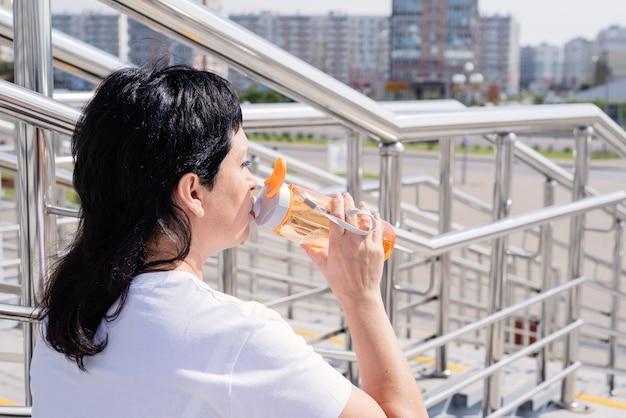 Trinkendes wasser der älteren frau nach dem training im freien