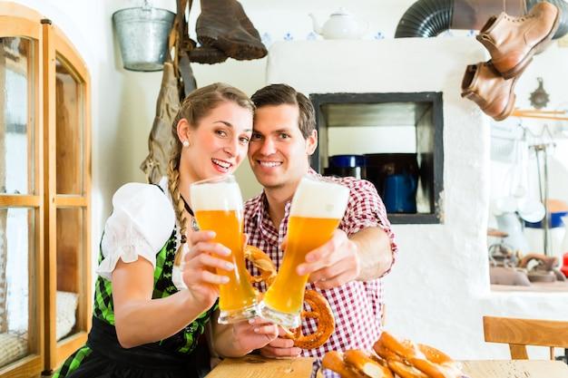 Trinkendes weizenbier der paare im bayerischen restaurant
