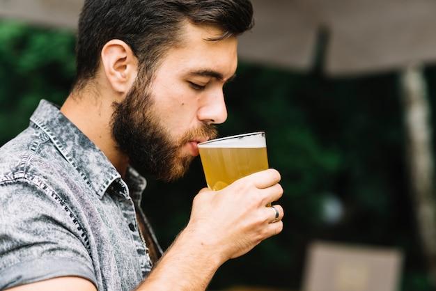 Trinkglas des gutaussehenden mannes bier an draußen