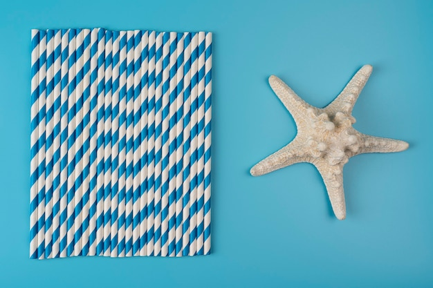 Trinkhalme auf blauem hintergrund. draufsicht auf bunte umweltfreundliche einwegstrohhalme aus papier für sommercocktails. mit seestern, umweltfreundliches urlaubskonzept