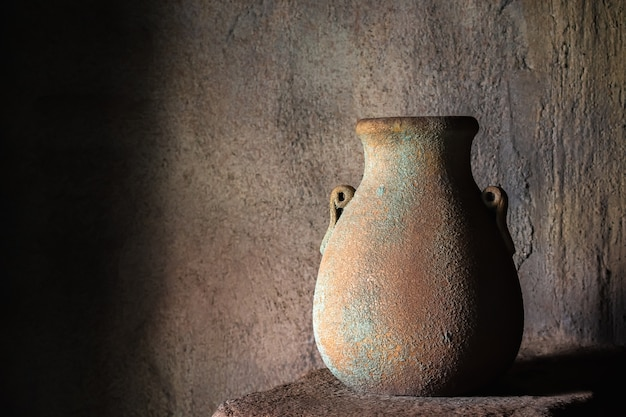 Trinkkrug aus steingut auf steinregal drinnen.