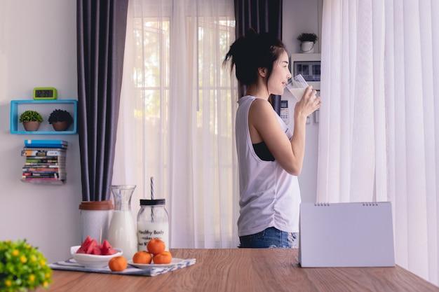 Trinkmilch der stehenden frau im wohnzimmer zu hause, junger asiatischer frauenlebensstil.