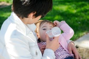Trinkmilch des Babys von der Babyflasche. Fütterungstochter der Mutter von der Flasche.