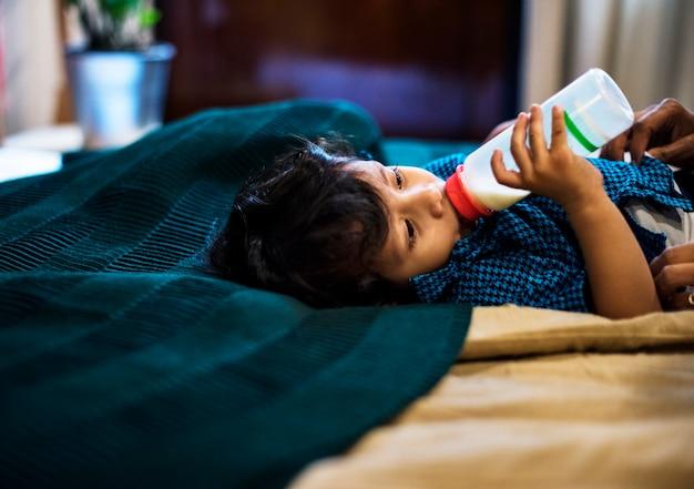 Trinkmilch des jungen indischen jungen von der flasche