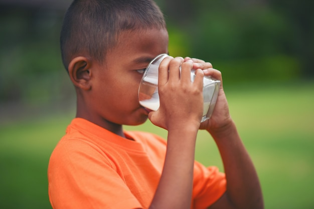 Trinkmilch des kleinen jungen im park