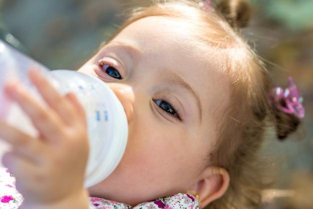 Trinkmilch des kleinen kindes von der babyflasche draußen