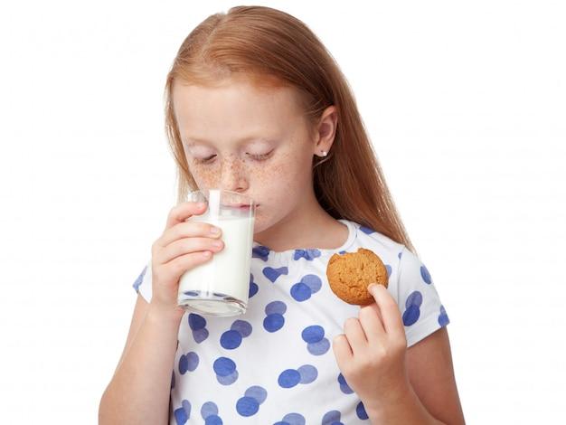 Trinkmilch des mädchens und essen eines plätzchens
