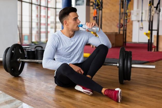 Trinkpause des jungen mannes nach übungen