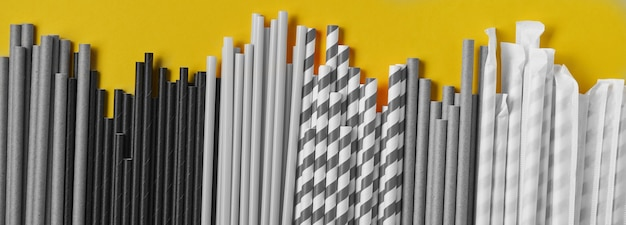 Trinkröhrchen aus papier und maisstärke, biologisch abbaubares material auf gelbem trendfarbenhintergrund 2021. null abfall und plastikfreies konzept. draufsicht.