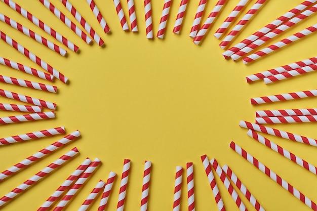Trinkröhrchen aus rotem und braunem papier und maisstärke, biologisch abbaubares material auf gelbem trendfarbe 2021 hintergrund. null-abfall-konzept. draufsicht.