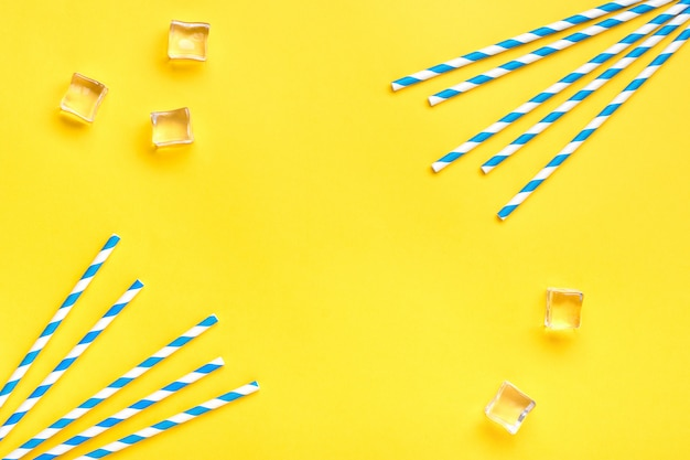 Trinkstrohhalme für party mit blauen streifen, eiswürfel auf gelbem hintergrund mit kopienraum.