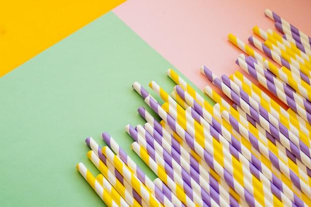 Trinkstrohhalme für sommercocktails auf heller pastellwand mit kopierraum. umweltfreundliche wiederverwendbare strohhalme. cocktailcubus aus papier. kraftpapierstroh zum trinken von kaffee oder tee