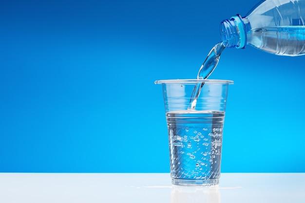 Trinkwasser aus der flasche in plastikbecher gießen