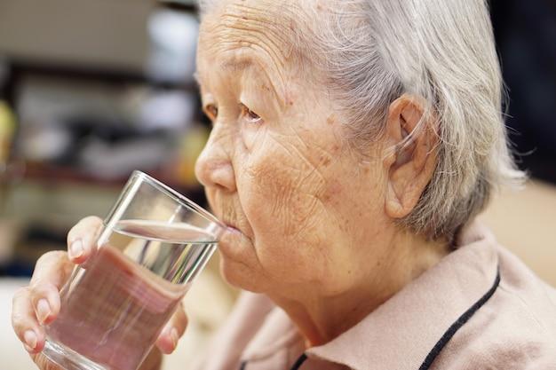 Trinkwasser der asiatischen älteren oder älteren alten frau, während sie auf der couch im haus sitzen. gesundheitswesen, liebe, fürsorge, ermutigung und empathie.