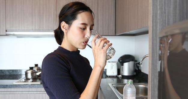 Trinkwasser der asiatischen frau auf glas in der küche