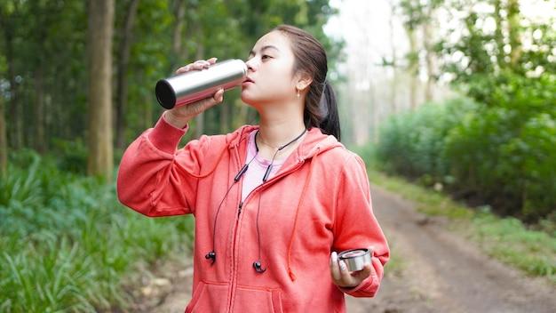 Trinkwasser der asiatischen frau nach übung auf grünem naturwaldhintergrund