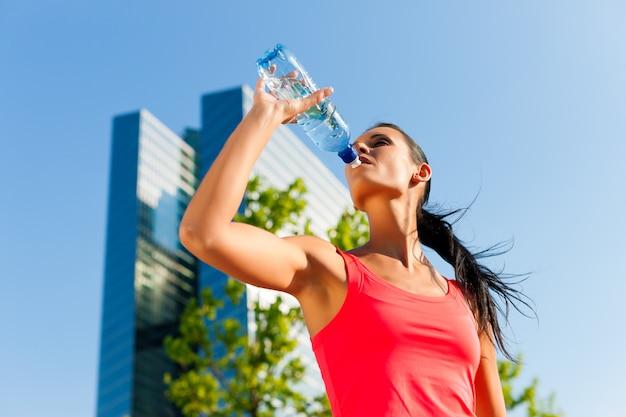 Trinkwasser der athletischen frau in einer städtischen landschaft