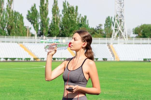 Trinkwasser der eignungsläuferfrau von einer sportflasche. energiegetränk beim training im stadion.