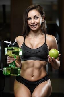 Trinkwasser der fitnessfrau beim training im fitnessstudio