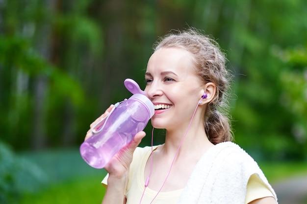 Trinkwasser der fitnessfrau nach dem lauftraining im sommerpark.