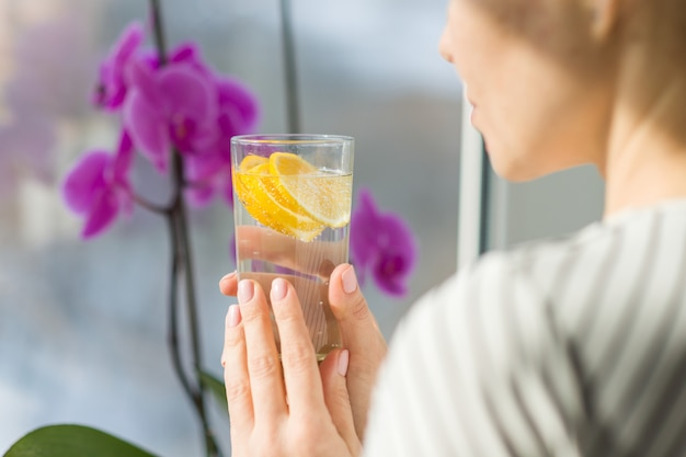 Trinkwasser der frau mit frischer organischer zitrone.