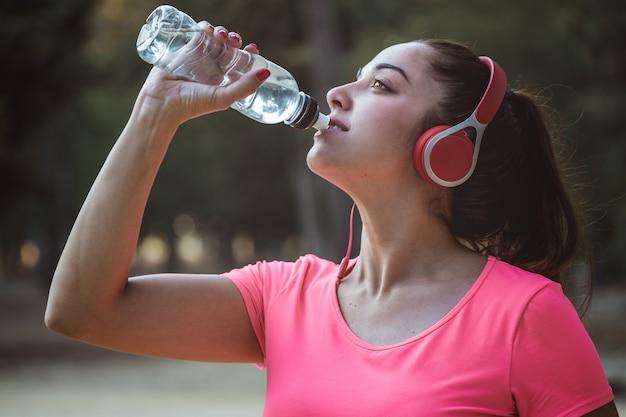 Trinkwasser der frau nach übung und hören musik mit einigen sturzhelmen im park