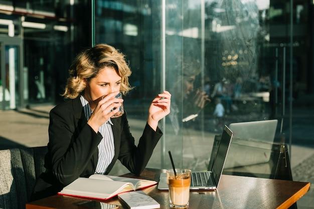 Trinkwasser der geschäftsfrau mit laptop- und schokoladenmilchshake auf schreibtisch