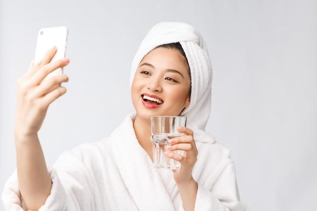 Trinkwasser der gesunden jungen schönen frau, natürliches make-up des schönheitsgesichtes mit haltendem mobiltelefon, lokalisiert über