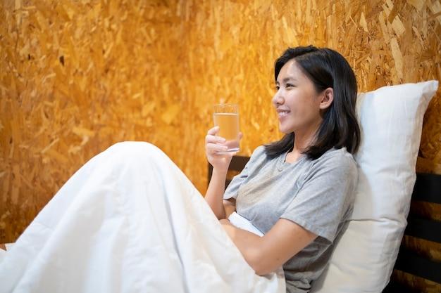 Trinkwasser der jungen asiatischen frau nach dem aufwachen