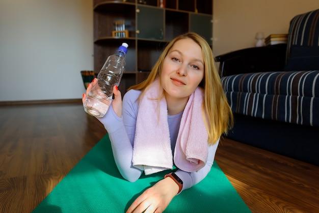 Trinkwasser der jungen frau nach übung. lächelndes attraktives fitnessmädchen mit handtuch nach dem training.