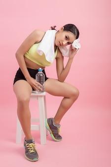 Trinkwasser der jungen schönen sitzfrau nach übung