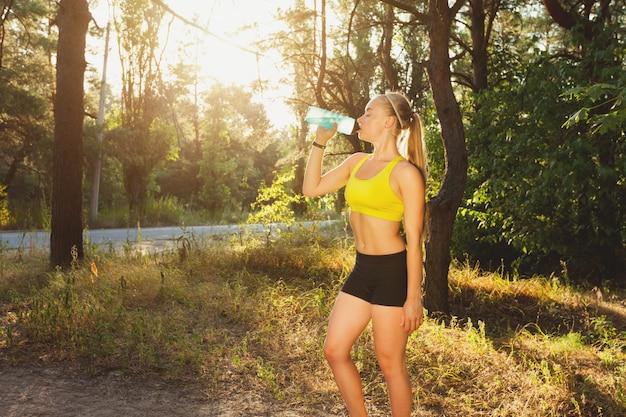 Trinkwasser der jungen sportlerin nach dem lauf