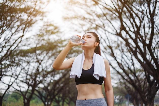 Trinkwasser der jungen sportlichen frau im park
