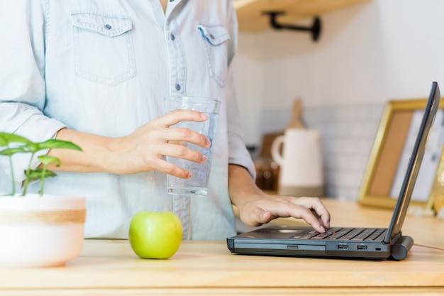 Trinkwasser der lateinamerikanischen frau, während sie ihren laptop benutzt